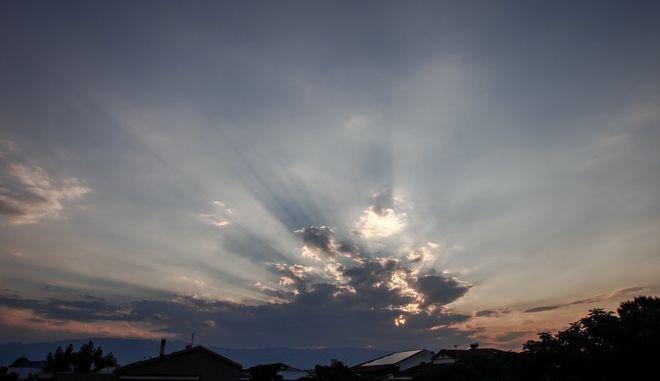 Οι ακτίνες του ηλίου ξεπροβάλουν μέσα από τα συννέφα πάνω από την πόλη των Τρικάλων. (EUROKINISSI/ΘΑΝΑΣΗΣ ΚΑΛΛΙΑΡΑΣ)