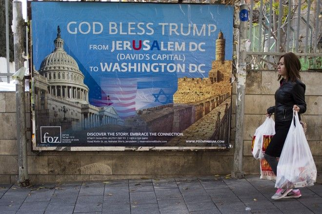 A woman walks past a poster praising U.S. President Donald Trumps recognition of Jerusalem as Israels capital, in Jerusalem, Thursday, Dec. 7, 2017. (AP Photo/Ariel Schalit)