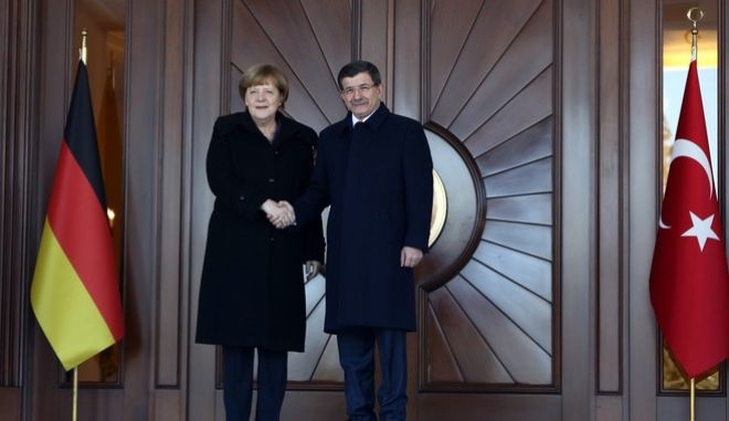 German Chancellor Angela Merkel, left, and Turkish Prime Minister Ahmet Davutoglu shake hands during a welcoming ceremony in Ankara, Turkey, Monday, Feb. 8, 2016. Merkel is meeting Davutoglu and other Turkish officials for talks on reducing the influx of migrants to Europe. Turkey, a key country on the migrant route to Europe, is central to Merkel's diplomatic efforts to reduce the flow. (AP Photo/Burhan Ozbilici)