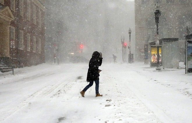 A pedestrian crosses the street in downtown Boston, Thursday, Jan. 4, 2018. A massive winter storm swept from the Carolinas to Maine on Thursday, dumping snow along the coast and bringing strong winds that will usher in possible record-breaking cold. (AP Photo/Michael Dwyer)