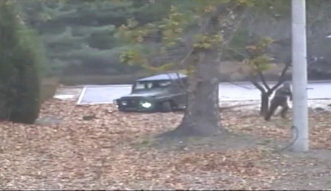 This image made from Nov. 13, 2017, surveillance video released by the United Nations command shows a North Korean soldier, second right, running from a jeep and later shot by North Korean soldiers at right. A North Korean soldier made a desperate dash to freedom in a jeep and then on foot, being shot at least five times as he limped across the border and was rescued by South Korean soldiers, according to dramatic video released by the U.S.-led U.N. command Wednesday, Nov. 22, 2017. (United Nations Command via AP)