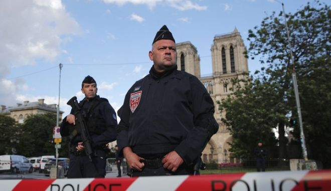 Police officers seal off the access to Notre Dame cathedral, seen in the background, after a man attacked officers with a hammer outside the famous landmark, in Paris, France, Tuesday, June 6, 2017. The Paris prosecutor's office said the investigation was opened Tuesday soon after the attack. The attacker was shot and wounded in the incident in one of France's most popular tourist areas. (AP Photo/Christophe Ena)