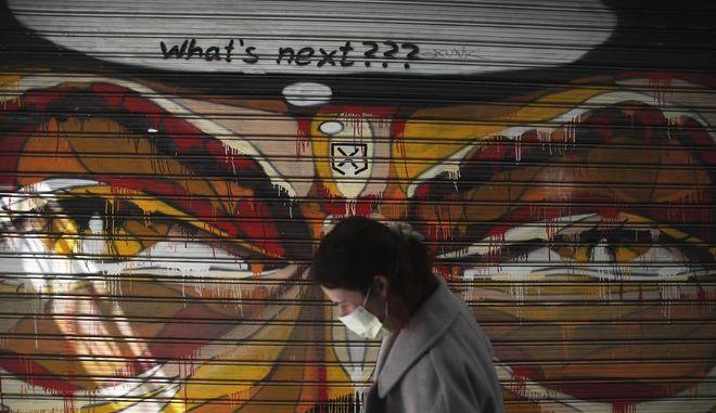 Γυναίκα με μάσκα σε δρόμο της Αθήνας.