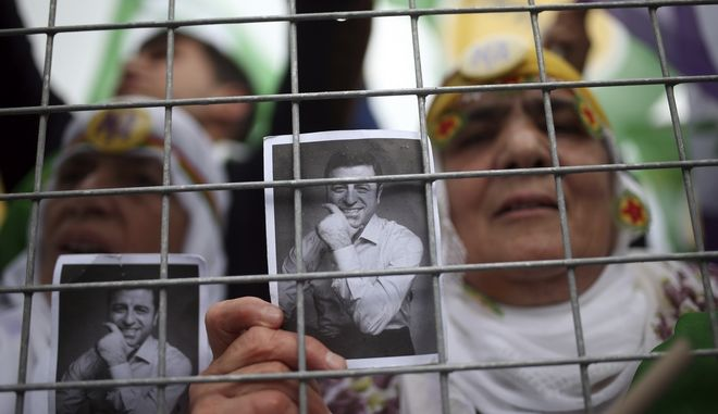 A supporter shows an image of jailed party leader Selahattin Demirtas during a referendum rally of pro-Kurdish Peoples' Democracy Party, in Diyarbakir, Turkey, Saturday, April 15, 2017. Turkey is heading to a contentious April 16 referendum on constitutional reforms to expand Erdogan's powers. (AP Photo/Emre Tazegul)