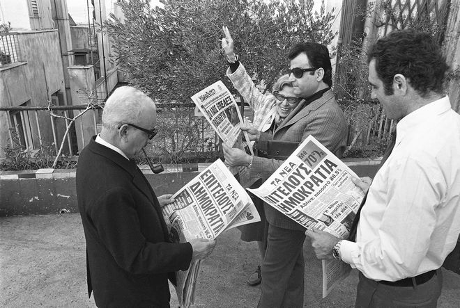 Athenians reading newspaper banner on the landslide defeat of the monarchy in Sunday's Plebiscite, December 9, 1974. Foreground headlines read.