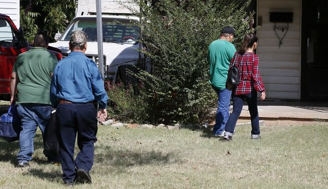 People arrive at the home of Magdiel Sanchez, the site of an officer involved shooting, in Oklahoma City, Wednesday, Sept. 20, 2017. Oklahoma City police officers who opened fire on a man who was approaching them holding a metal pipe didn't hear witnesses yelling that the man was deaf, police Capt. Bo Mathews said at a news conference. (AP Photo/Sue Ogrocki)