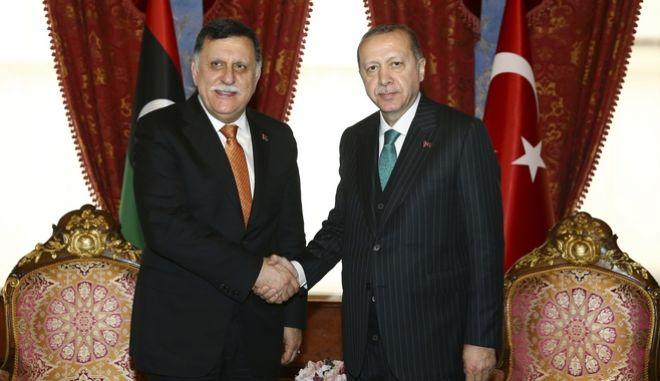 Ο Ταγίπ Ερντογάν και ο Φάγεζ αλ-Σάρατζ κάνουν χειραψία.