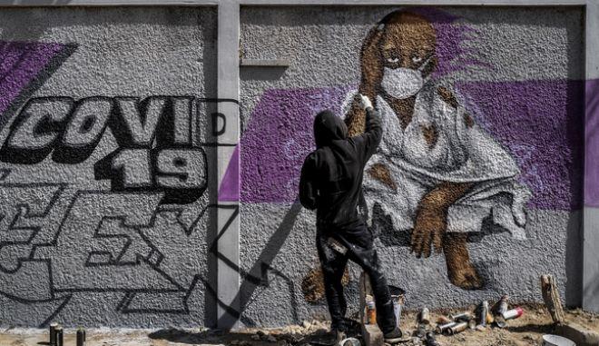 Νεαρό δημιουργεί γκράφιτι για τον κορονοϊό στη Σενεγάλη