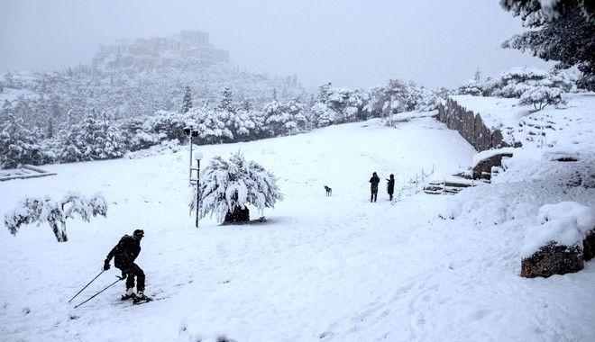 Σκι στον λόφο της Πνύκας με θέα τη χιονισμένη Ακρόπολη