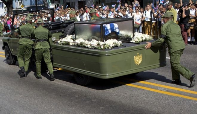 Soldiers push the jeep and trailer carrying the ashes of the late Fidel Castro after the jeep briefly stopped working during Castro's funeral procession near Moncada Fort in Santiago de Cuba, Cuba, Saturday, Dec. 3, 2016. Castro's ashes will be interred Sunday in Santiago, ending a nine-day period of mourning that saw Cuba fall silent as thousands paid tribute to photographs of Castro and sign oaths of loyalty to his socialist, single-party system. (AP Photo/Rodrigo Abd)
