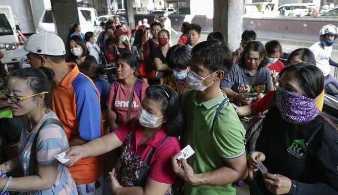 Άνθρωποι έρχονται στην ουρά για να αγοράσουν προστατευτικές μάσκες προσώπου σε κατάστημα στη Μανίλα
