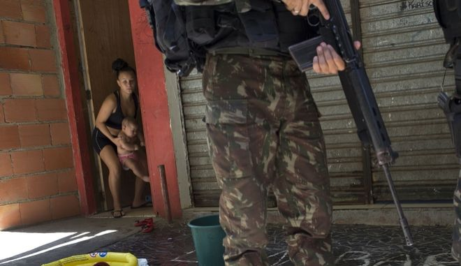 A woman moves her baby inside while a soldier patrols during an operation at the Rocinha slum, in Rio de Janeiro, Brazil, Tuesday, Oct. 10, 2017. More than 1,000 Brazilian police and soldiers are searching Rio de Janeiro's largest slum for weapons and ammunition amid a crackdown on drug gangs. In recent weeks, a series of intense shootouts led Brazilian authorities to ask the military for help patrolling the perimeter of Rocinha. (AP Photo/Silvia Izquierdo)