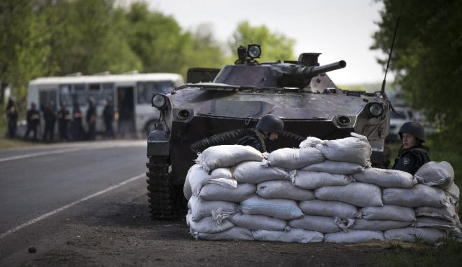 Ukrainian government troops guard a checkpoint near the village of Dolina, 30 kilometers (18 miles) from Slovyansk, eastern Ukraine, Thursday, May 1, 2014. Russian state news media were quick to dismiss the protests as the work of Ukrainian neo-Nazis, a particularly loaded accusation because Ukrainian nationalists collaborating with the Nazis are blamed for horrific reprisal attacks during World War II.(AP Photo/Alexander Zemlianichenko)