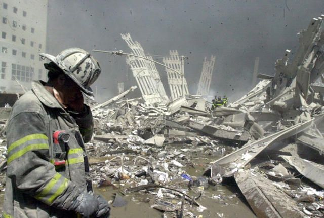 Firefighter walks through the rubble of the World Trade Center after it was struck by a commercial airliner in a terrorist attack. A hijacked American Airlines Boeing 767, originating from Boston's Logan Airport, struck 1 World Trade Center (north tower) at 8:45 a.m. At 9:03 a.m., a United Airlines 767, also hijacked in Boston, crashed into 2 World Trade Center (south tower).The second tower came down 39 minutes after the first.