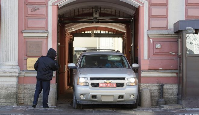 A van leaves the U.S. consulate as a Russian police officer, left, guards the entrance, in St. Petersburg, Russia, Friday, March 30, 2018. Russia announced the expulsion of more than 150 diplomats, including 60 Americans, on Thursday (AP Photo/Dmitri Lovetsky)