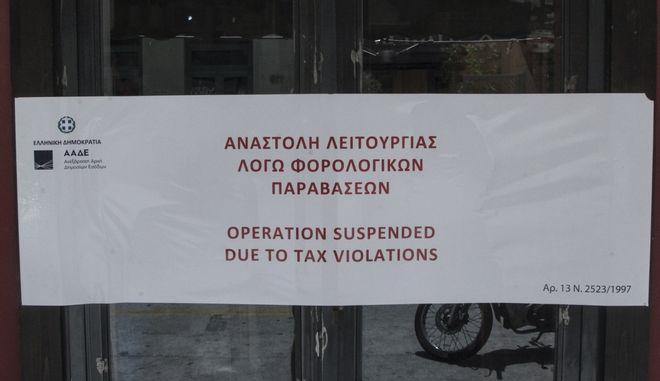 """Το σχετικό αυτοκόλλητο στην είσοδο καταστήματος που βάζει η ΑΑΔΕ όταν επιβάλει """"λουκέτο"""" λόγω παραβάσεων."""