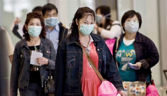 Περαστικοί φορούν μάσκες για προστασία από μετάδοση ιού. Φωτό αρχείου