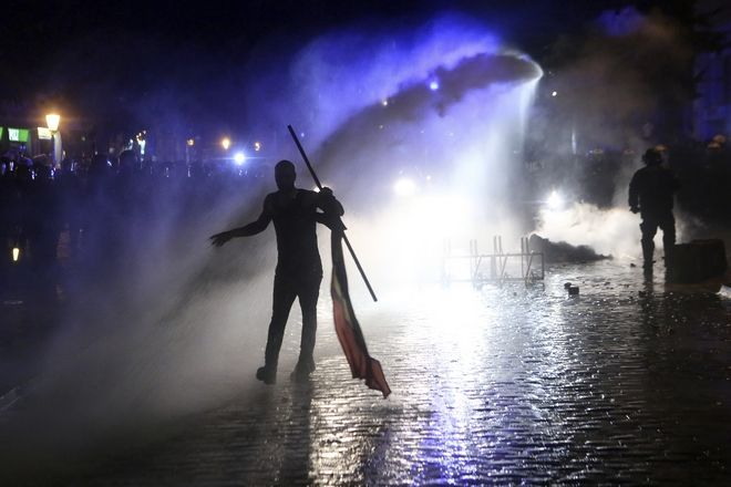In this July 6, 2017 photo a protester is silhouetted against a water cannon of the police during violent demonstrations on the eve of the G-20 summit in Hamburg, northern Germany.  The leader of the group of 20 meet Friday and Saturday in Hamburg.  (Bodo Marks/dpa via AP)