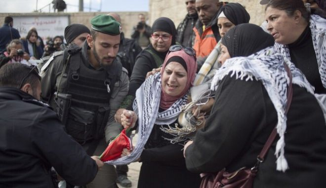 Israeli police officers try to remove a Palestinians flag from Palestinian women protesting outside the Damascus Gate in Jerusalem Old City, Thursday, Dec. 7, 2017. Clashes between hundreds of Palestinian protesters and Israeli troops erupted across the West Bank on Thursday while demonstrators in Gaza burned posters of President Donald Trump and Israeli Prime Minister Benjamin Netanyahu, as well as Israeli and U.S. flags. (AP Photo/Ariel Schalit)
