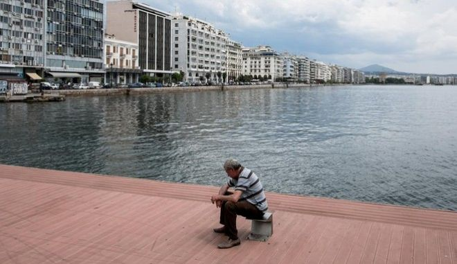 An elderly man sit on the dock at the port of Thessaloniki, Greece on 29 May 2014.