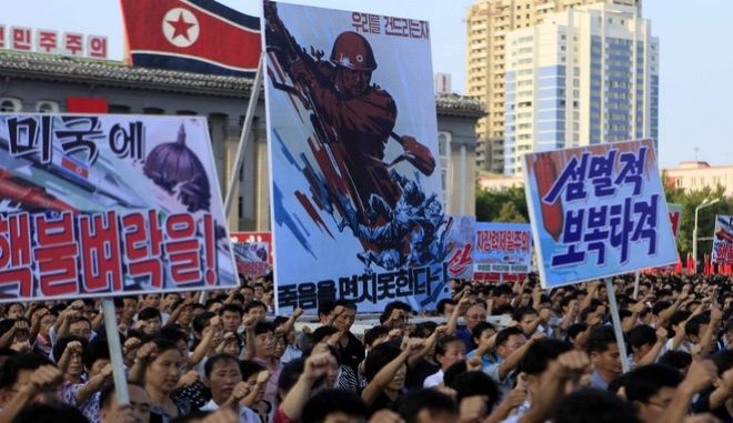 ADDS TRANSLATION OF SIGNS - Tens of thousands of North Koreans gathered for a rally at Kim Il Sung Square carrying placards and propaganda slogans as a show of support for their rejection of the United Nations' latest round of sanctions on Wednesday Aug. 9, 2017, in Pyongyang, North Korea. Propaganda signs, from left to right: Strike the United States with nuclear thunderbolt!; Those who touch us will not escape death; A revenge attack of annihilation. (AP Photo/Jon Chol Jin)