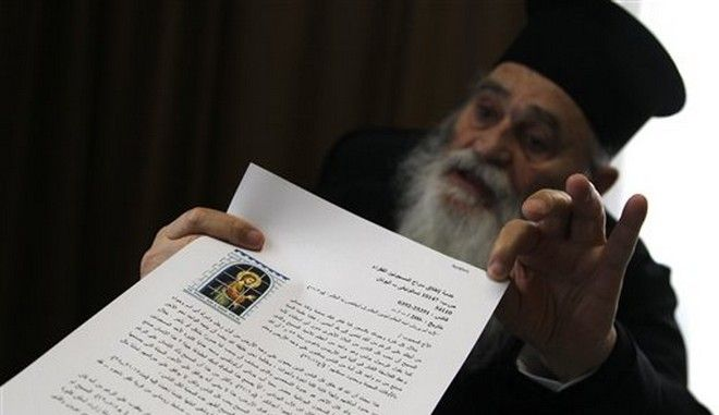In this Sunday, Feb. 2, 2014 Father Gervasios holds up a letter, in Arabic, copies of which are handed out to all prisoners his charity frees, in their own language, explaining why they receive the help in the northern port city of Thessaloniki. The soft-spoken 83-year-old with a long white beard and black robes has helped more than 15,000 convicts secure their freedom over nearly four decades, according to records kept by his charity. The Greek rules apply only to people convicted of offences that carry a maximum five-year sentence, such as petty fraud, bodily harm, weapons possession, illegal logging, resisting arrest and minor drugs offences. (AP Photo/Nikolas Giakoumidis)