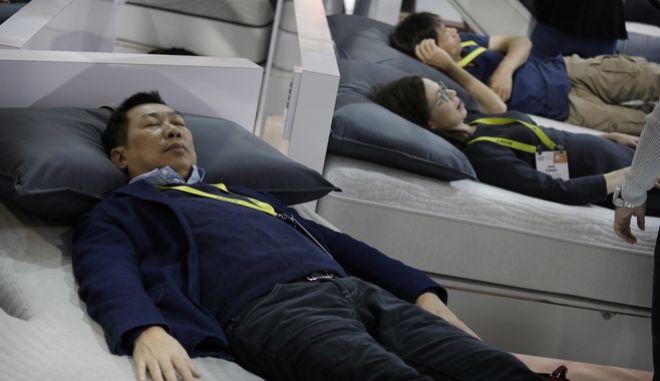 Πελάτες δοκιμάζει κρεβάτι κατά τη διάρκεια του CES International