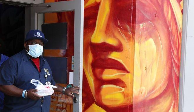 Άντρας με μάσκα μπροστά από γκράφιτι στις ΗΠΑ