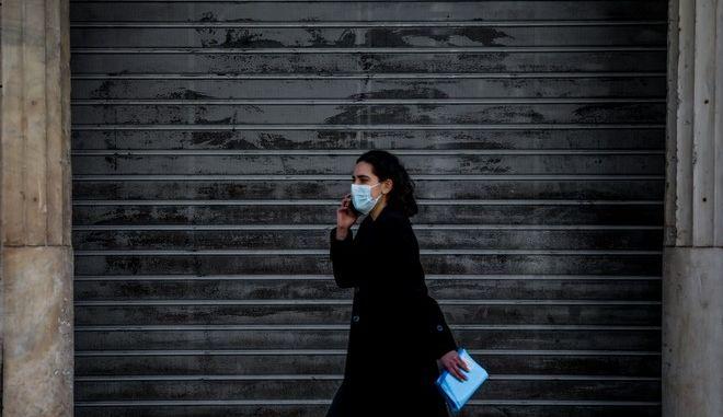 Γυναίκα με μάσκα μπροστά από κλειστή επιχείρηση