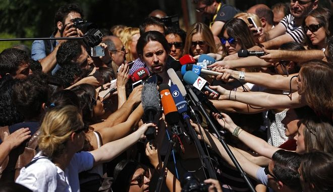 Spain's Podemos coalition party leader Pablo Iglesias, center,  talks to journalists after casting his vote for the national elections in Madrid, Sunday, June. 25, 2016. Spaniards headed to the polls Sunday for an unprecedented repeat election that aims to break six months of political deadlock after a December ballot left the country without an elected government.(AP Photo/Francisco Seco)