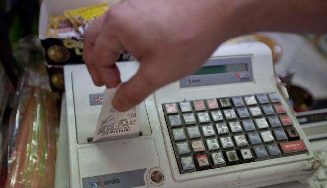 Πελάτης παραλαμβάνει την απόδειξη σε κατάστημα.