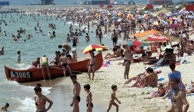 Bulgarians gather on a beach of the Black Sea port of Varna, some 480 kilometer (298 miles) east of Sofia on Wednesday, July 17, 2002 as temperature reached 39 degrees Celsius, that is a record for the last 100 years for this town. Health officials in Bulgaria urged people to stay in the shade and drink lots of liquids to avoid falling victim to a heat wave sweeping across the country. (AP Photo/Petar Petrov)