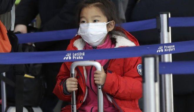 Ένα κορίτσι στο Αεροδρόμιο της Τσεχίας φοράει μάσκα, περιμένοντας στην ουρά για check in για πτήση προς τη Σαγκάη.