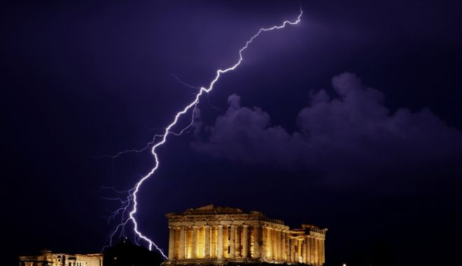 ** CORRECTS SPELLING OF THE TEMPLE'S NAME **  A flash of lightning illuminates the sky over  the 2,500-year-old Ancient Parthenon temple, at the Acropolis hill during a heavy rainfall in Athens, early Monday, June 28, 2010.(AP Photo/Petros Giannakouris)