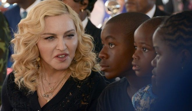US singer Madonna, left, sits with her adopted children David, Stella and Mercy, at the opening of The Mercy James Institute for Pediatric Surgery and Intensive Care, located at the Queen Elizabeth Central Hospital in the city of Blantyre, Malawi, Tuesday, July 11, 2017. Madonna was in Malawi on Tuesday for the official opening of a hospital children's wing funded by her charity and named after one of the four children the pop star has adopted from the impoverished southern African nation. (AP Photo Thoko Chikondi)