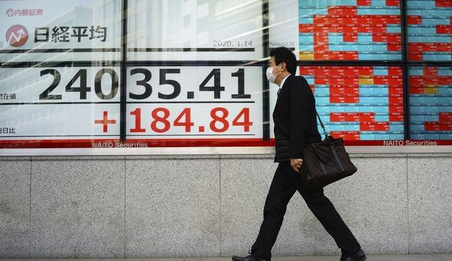 Άνδρας μπροστά από πίνακα ηλεκτρονικών συναλλαγών στην Ιαπωνία