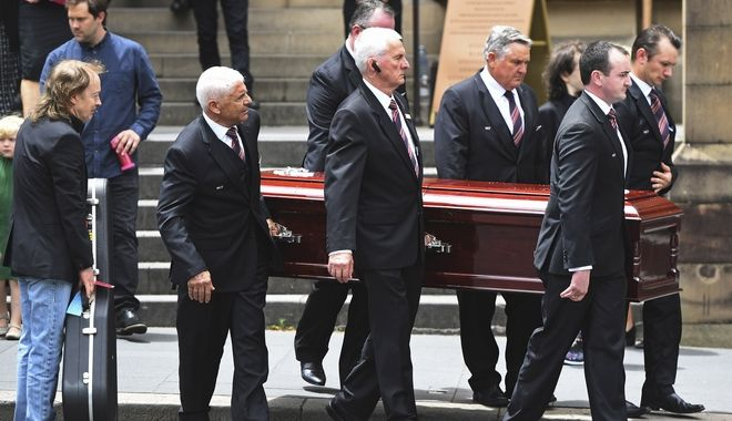 Angus Young, left, holds a guitar as the casket of his brother AC/DC co-founder and guitarist Malcolm Young is carried to a hearse following his funeral at St. Mary's Cathedral in Sydney, Tuesday, Nov. 28, 2017. Malcolm along with his brother Angus Young founded the iconic rock group AC/DC. (Dean Lewins/AAP via AP)