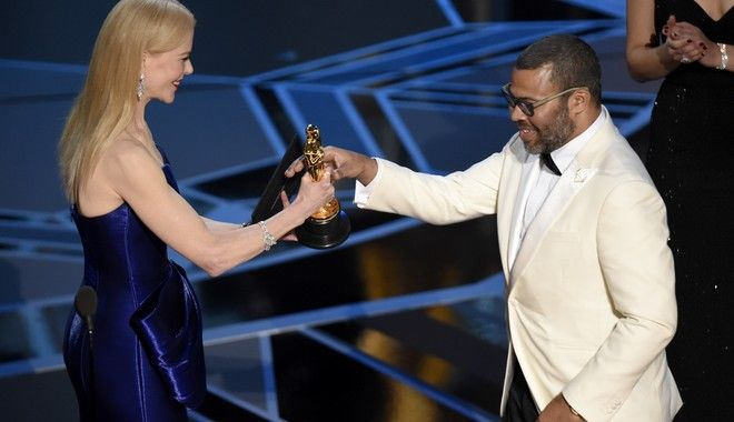 "Nicole Kidman, left, presents Jordan Peele with the award for best original screenplay for ""Get Out"" at the Oscars on Sunday, March 4, 2018, at the Dolby Theatre in Los Angeles. (Photo by Chris Pizzello/Invision/AP)"