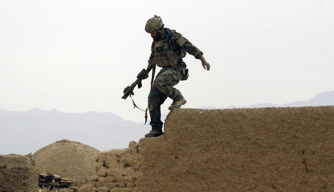 FILE - In this Sunday, Nov. 1, 2009 file photo, a member of U.S. special operations forces climbs down from a compound wall during a joint patrol with Afghan National Army soldiers in Shewan, a former Taliban stronghold,  in Afghanistan's Farah province. Defense Secretary Ash Carter told Congress on Tuesday, Dec. 2, 2015 that the U.S. military will deploy a new special operations force to Iraq to step up the fight against Islamic State militants, who are determined to hold territory they have seized in Iraq and Syria. (AP Photo/Maya Alleruzzo, File)