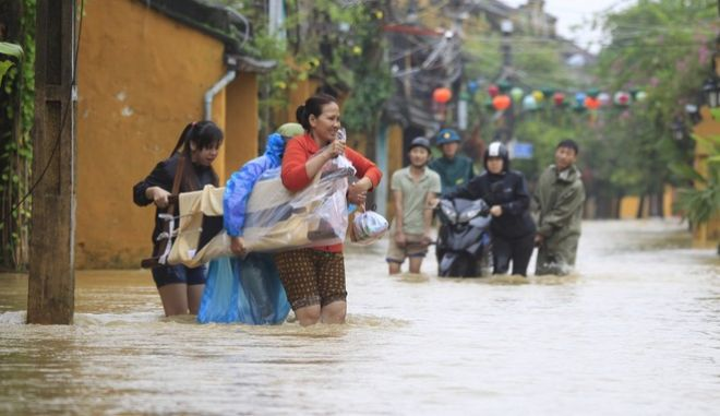 People move furniture in a flooded street in Hoi An, Vietnam, Monday, Nov. 6, 2017. A powerful typhoon that rocked Vietnam has killed dozens of people and caused extensive damage to the country's south-central region ahead of the APEC summit that will draw leaders from around the world, the government said Monday. (AP Photo/Hau Dinh)