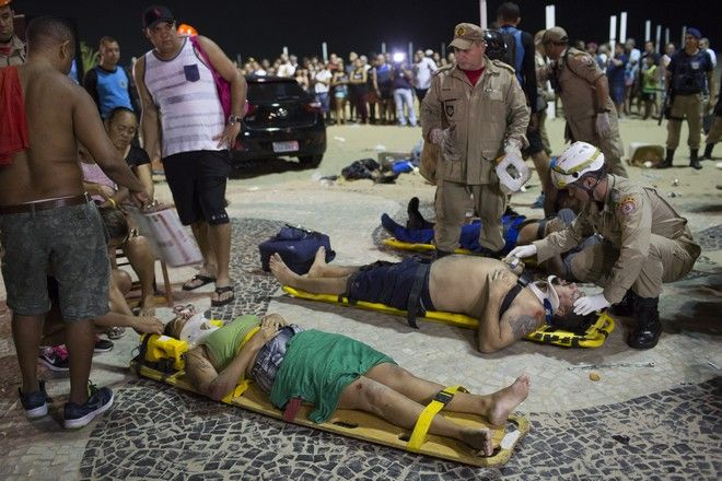Firefighters give the first aid to people that were hurt after a car drove into the crowded seaside boardwalk along Copacabana beach in Rio de Janeiro, Brazil, Thursday, Jan. 18, 2018. Military police said on Twitter that at least 11 people were injured and that the driver has been taken into custody. (AP Photo/Silvia Izquierdo)