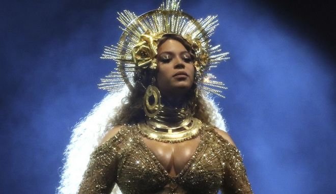 FILE - In this Feb. 12, 2017 file photo, Beyonce wears a gold, royal crown and neck collar and a Peter Dundas gown an embroidered portrait of herself as she performs at the 59th annual Grammy Awards in Los Angeles. (Photo by Matt Sayles/Invision/AP, File)