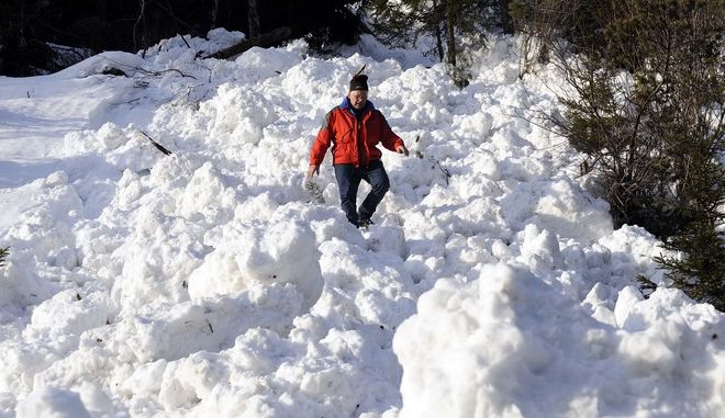 A man is seen walking on the snow after an avalance hit the main street between Lofer and Waidring, in the Austrian province of Tyrol, Sunday March 1, 2009.  Nobody was hurt in the avalanche. (AP Photo/ Kerstin Joensson)