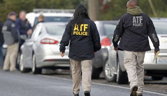 Officers from the federal Bureau of Alcohol, Tobacco, Firearms and Explosives arrive Monday, Jan. 8, 2018, in Frederickson, Wash., near the scene of the fatal shooting of a Pierce County Sheriff's deputy overnight. One suspect in the shooting was found dead at the scene, but another got away, authorities said. (AP Photo/Ted S. Warren)