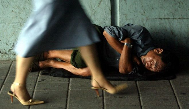 A homeless Chinese man curls up to sleep at an underpass as a woman walks past in Beijing, China, Thursday, July 29, 2004.  Critics fear the growing divide between the rich and the poor may lead to social disturbance. (AP Photo/Ng Han Guan)