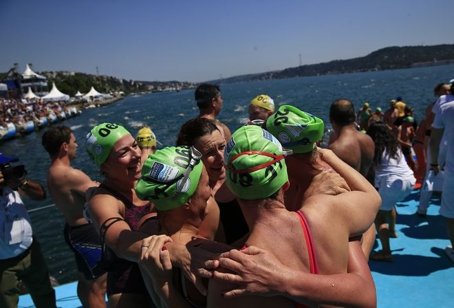 Athletes celebrate after they swam from Asia to Europe in the Bosphorus strait during the Bosporus Cross-Continental Swimming Race in Istanbul, Sunday, July 23, 2017. Over 2,000 open-water competitors plunged into the water from a ferry docked on the city's Asian side and swam from Asia to Europe across Istanbul's Bosphorus Strait for about 6.5km in this cross-continental event. (AP Photo/Lefteris Pitarakis)