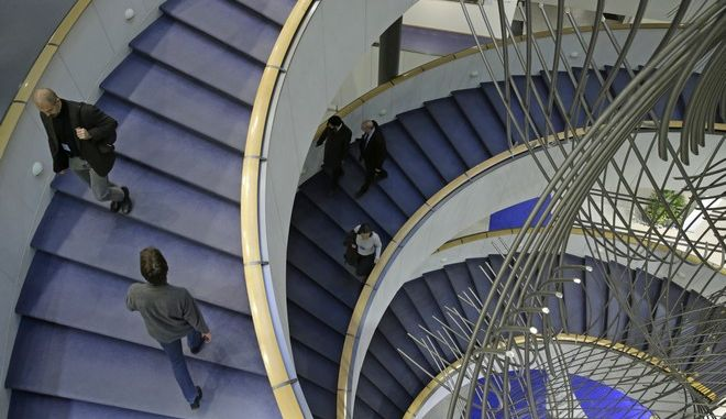 People walk the stairs of the European Parliament building, in Brussels on Monday, Nov. 17, 2014. The European Parliament has three places of work: in Brussels, the city of Luxembourg and Strasbourg in France. The daily Committee meetings are held in Brussels. (AP Photo/Yves Logghe)