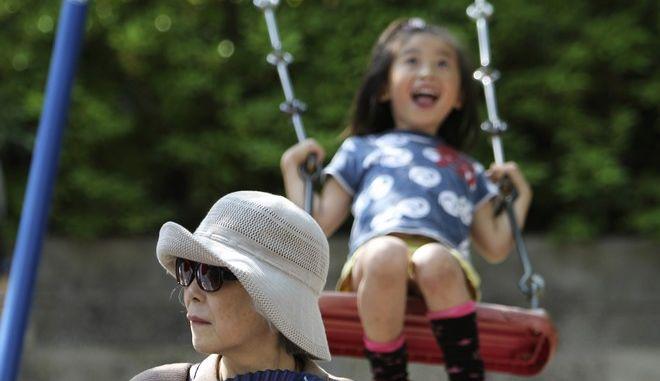 Γυναίκα με γυαλιά και καπέλο στην Ιαπωνία και ένα παιδί που κάνει κούνια πίσω της