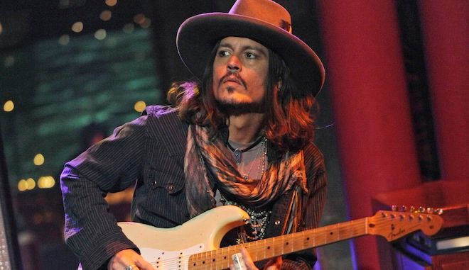 """In this photo provided by CBS, actor Johnny Depp plays slide guitar on the set of the Late Show with David Letterman. Thursday Feb. 21, 2013 in New York. Depp accompanied musical guests """"Bill Carter and the Blame."""" (AP Photo/CBS, Jeffrey R. Staab) MANDATORY CREDIT; NO SALES; NO ARCHIVE; FOR NORTH AMERICAN USE ONLY"""