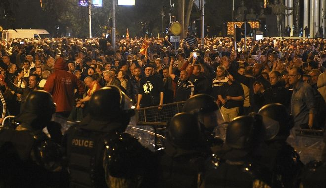 Police cordon blocks protesters to enter into the parliament building in Skopje, Macedonia, Thursday, April 27, 2017. Chaos swept into Macedonia's parliament Thursday as demonstrators stormed the building and attacked lawmakers to protest the election of a new speaker despite a months-old deadlock in efforts to form a new government. (AP Photo/Dragan Perkovski)